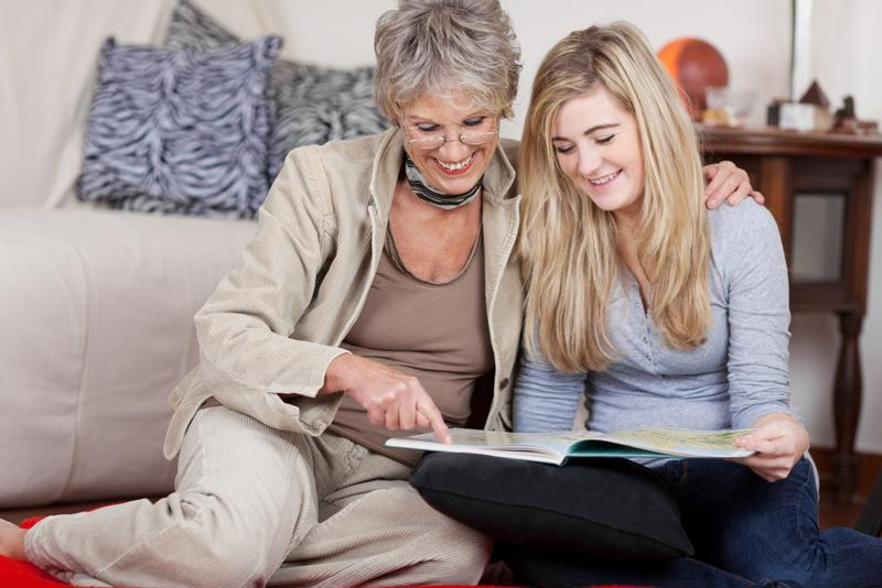 grandmother reading with teenage granddaughter