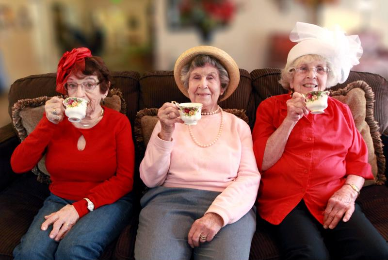 Three seniors sitting on couch at Edgewood drinking tea.