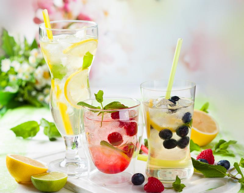 Glasses full of water with fruit and mint leaves mixed in.