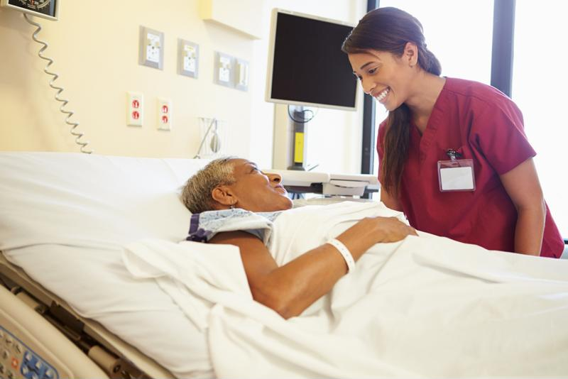 Nurse standing over patient smiling.