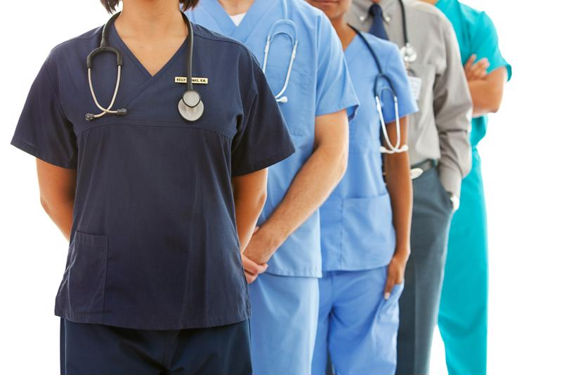 People wearing scrubs and stethoscopes standing in a line, without view of their faces.