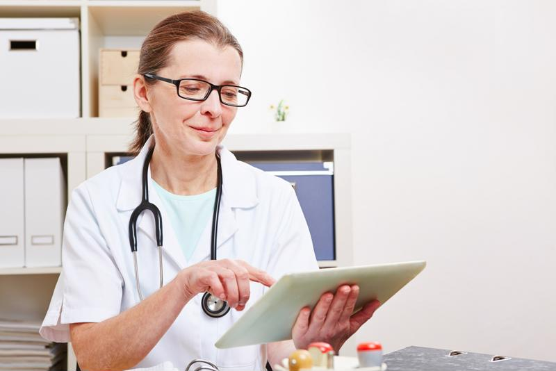 Female doctor looking over patient information on a tablet.