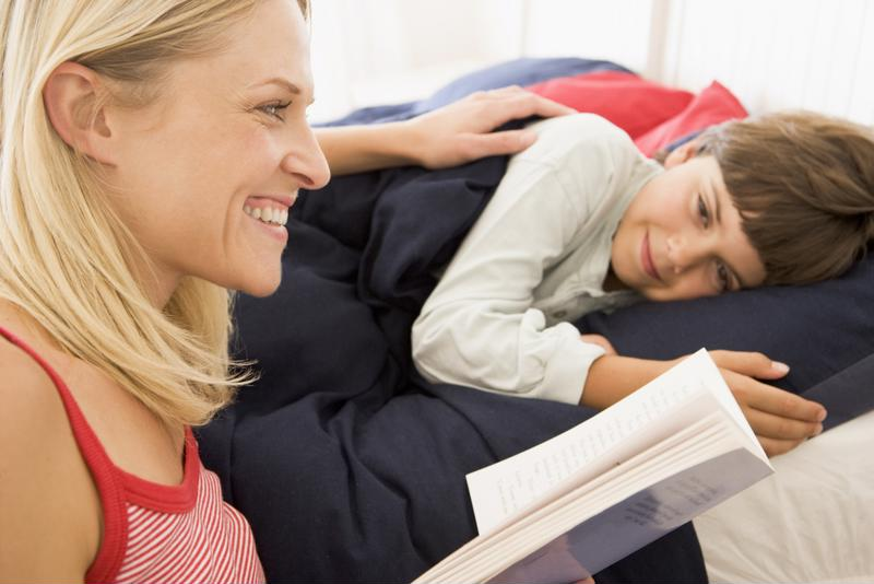 Mother reading to young son in bed.