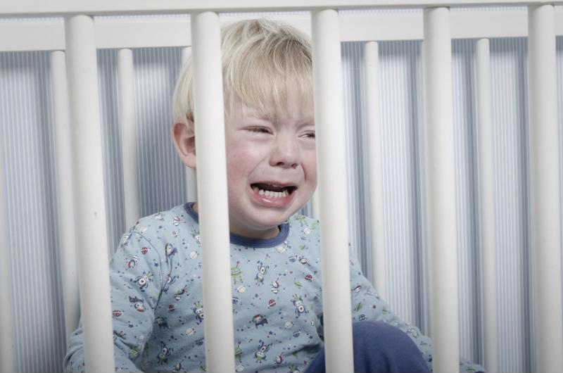 A baby boy crying in a crib.