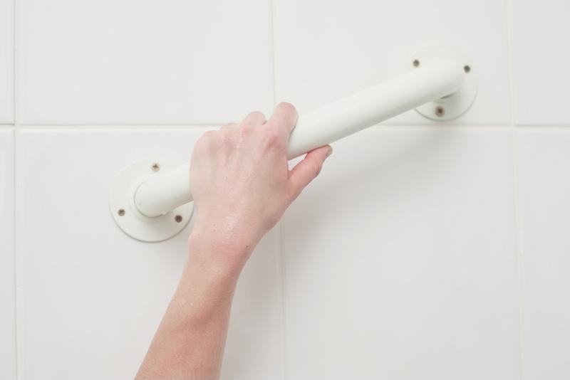 Hand holding onto bathtub grab bar.