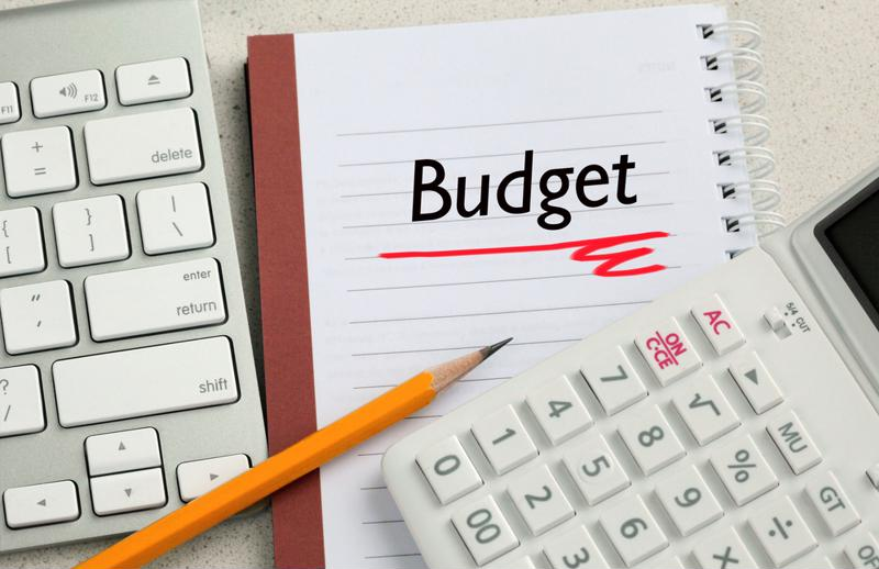 "Word ""budget"" on notepad with pencil and calculator."