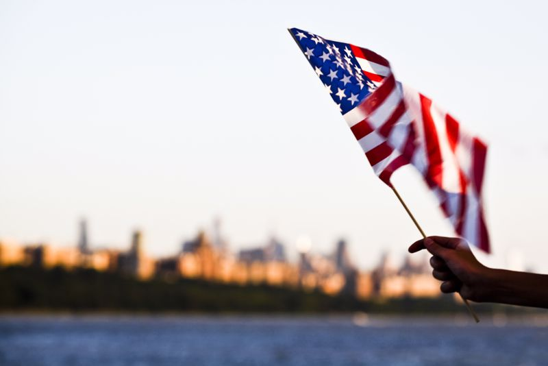 American flag waving with a city in the background.