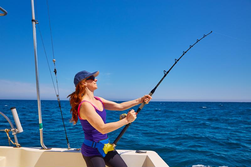 A woman stands on a boat and reels in a fish.