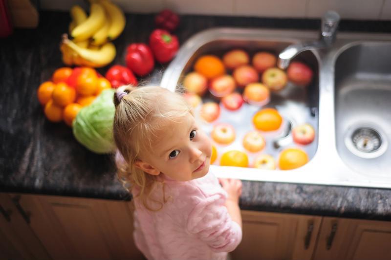 A little girl washing fruit.