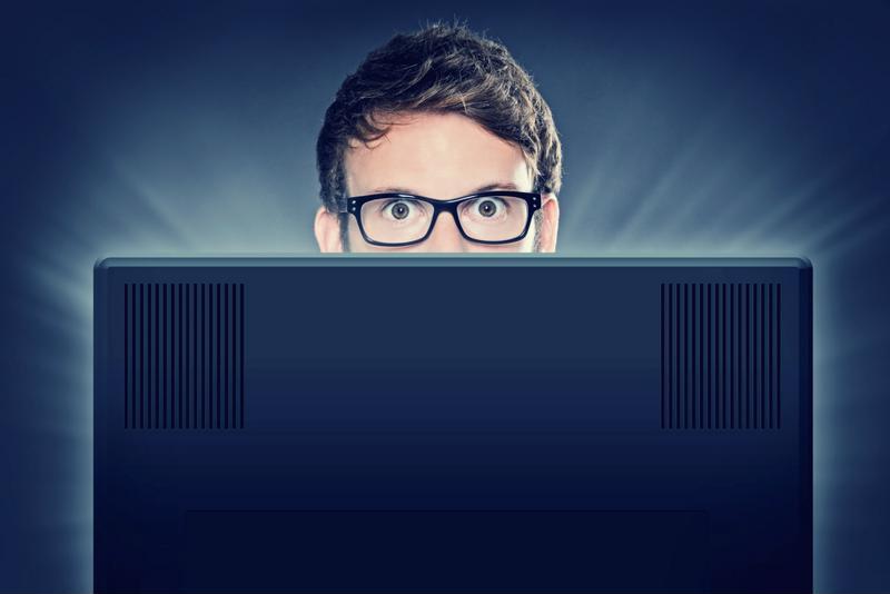 Man peering over computer screen