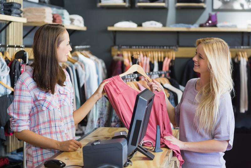 woman buying a shirt from a saleswoman in a retail store