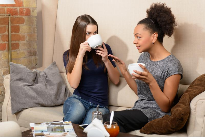 Two women having a discussion over tea in a coffee shop.