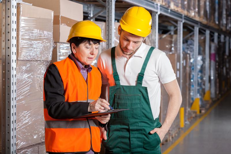 Two manufacturing workers discuss cybersecurity policies.