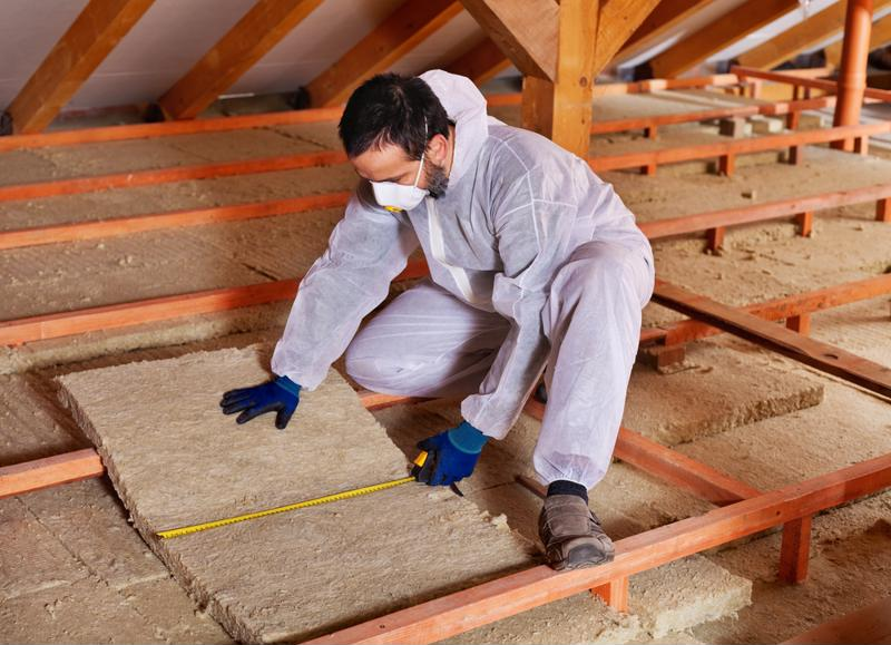 A worker lays installation in a house.