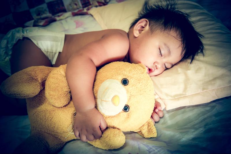 An infant sleeping with a teddy bear.