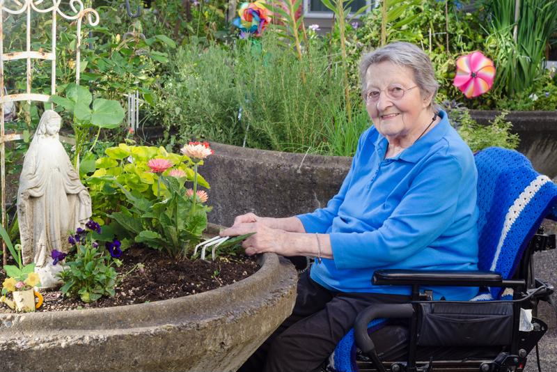Senior woman in wheel chair gardening.