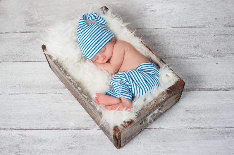 A newborn baby sleeping in a vintage crate with a furry blanket.