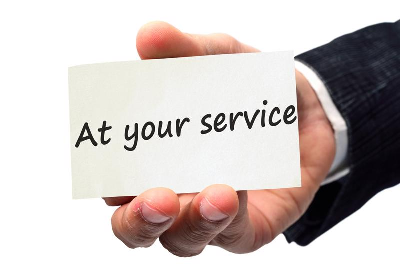 "Hand holding a business card with the words ""At your service"" on it."