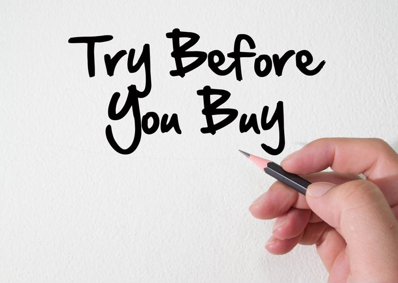 """Try before you buy"" next to hand holding a pencil,"