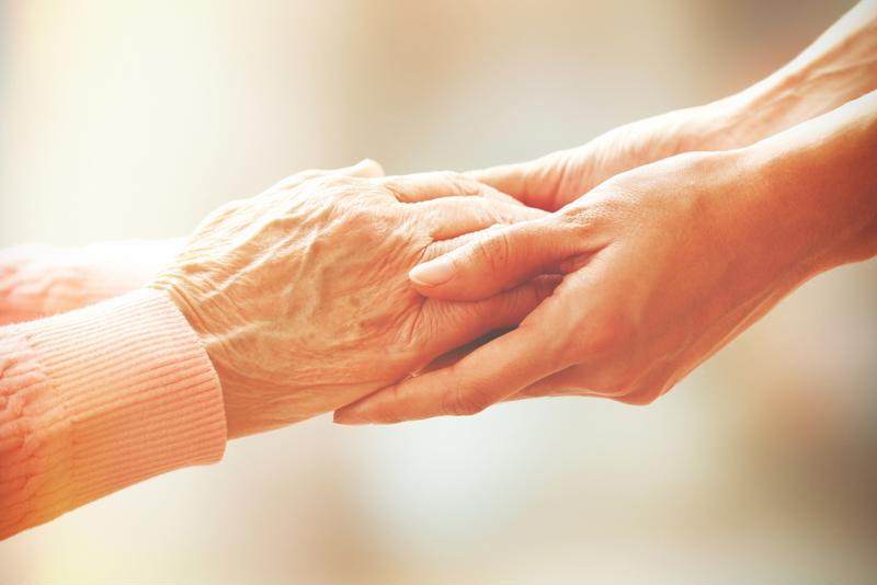 Senior holding hands of home health aide.