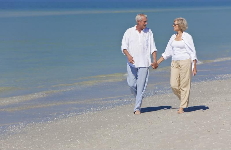 Happy senior couple walking together on beach.