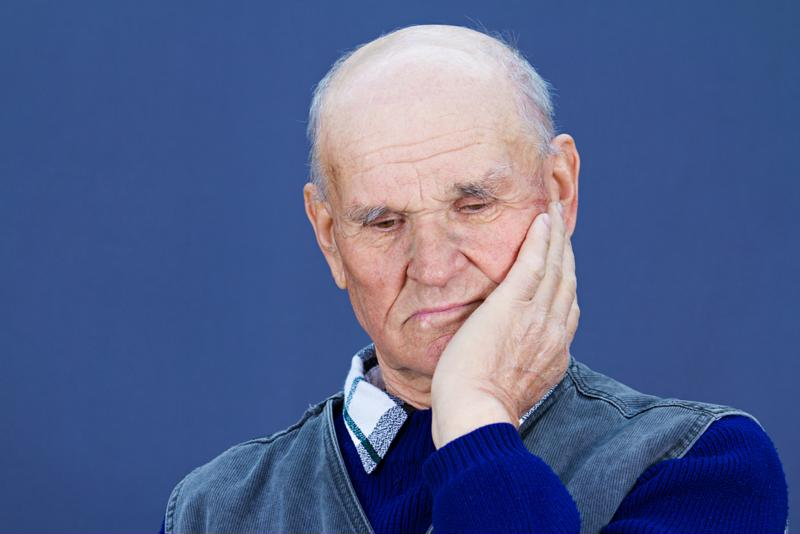 Senior man with dementia on blue background.