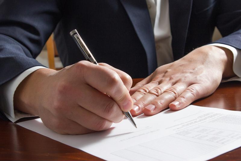 Hand using pen to sign paper.