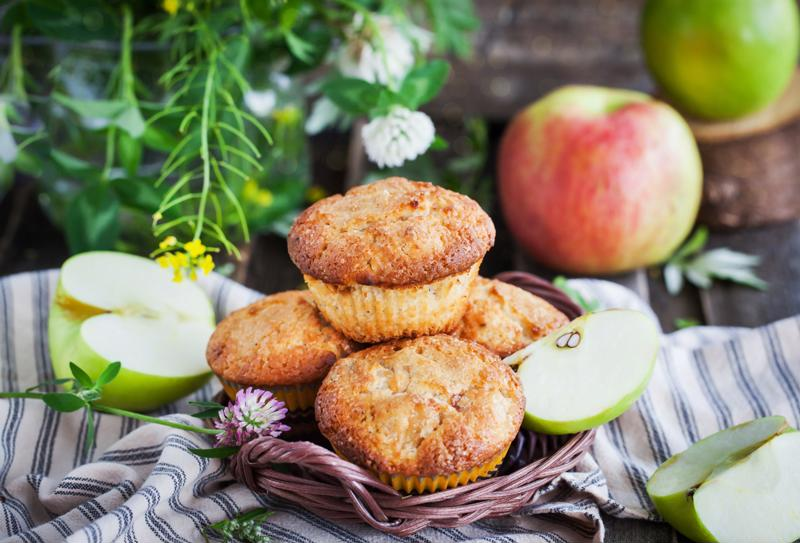Apple mini muffins are set in a wicker basket alongside apple slices.