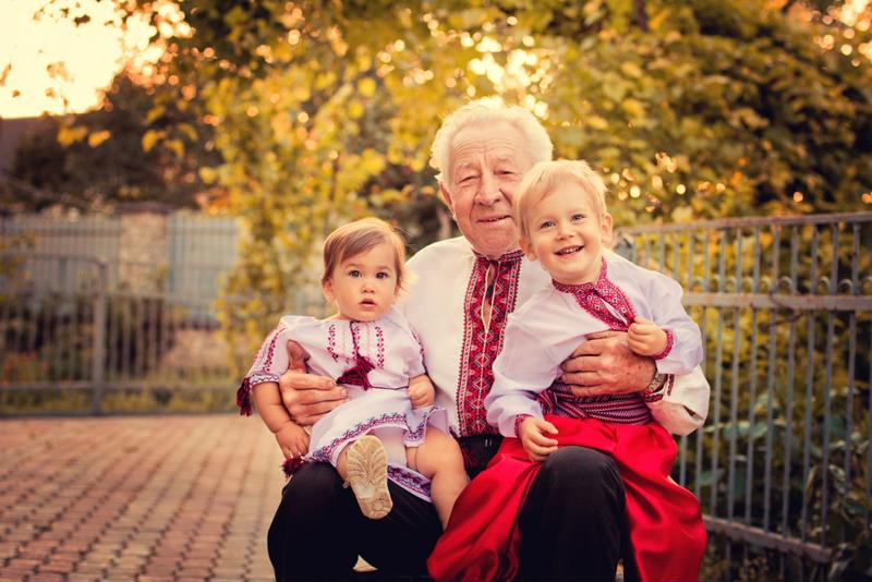 A grandfather with two grandchildren in the park.