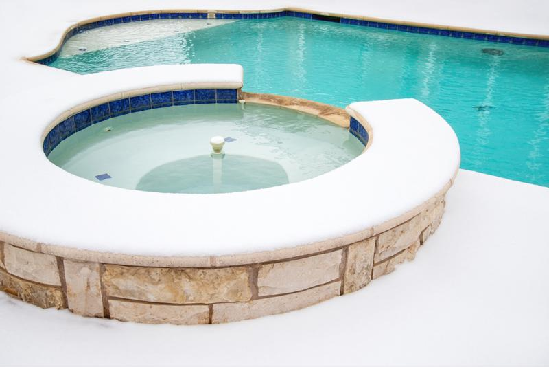An outdoor hot tub is connected to a larger pool in a sunny day.