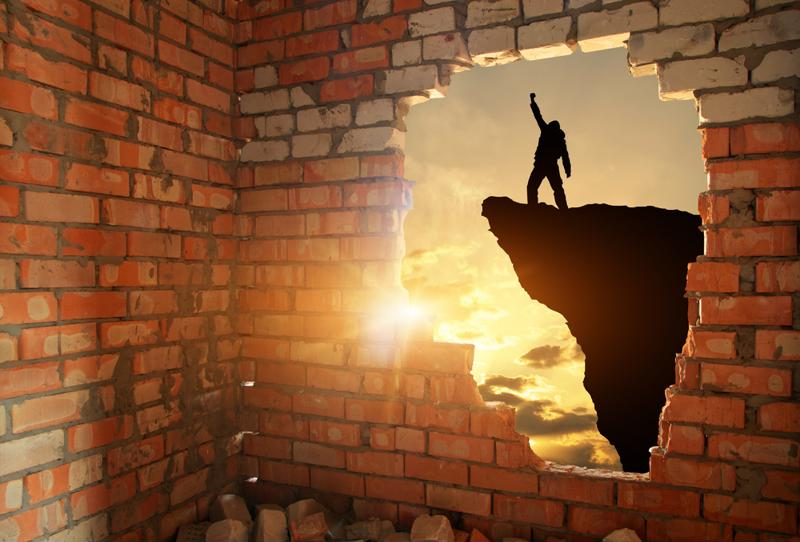 Hole in a brick wall reveals shadow silhouette of a person with their fist raised victoriously in the air, standing on the edge of a cliff.