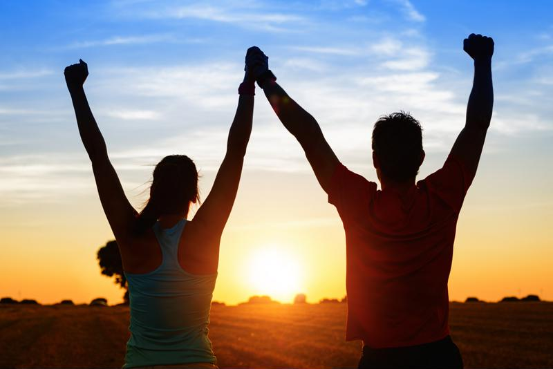 Two people, arms up, holding hands with the sun and sky in the background.