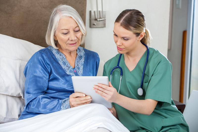 Nurse looking at tablet with senior patient.