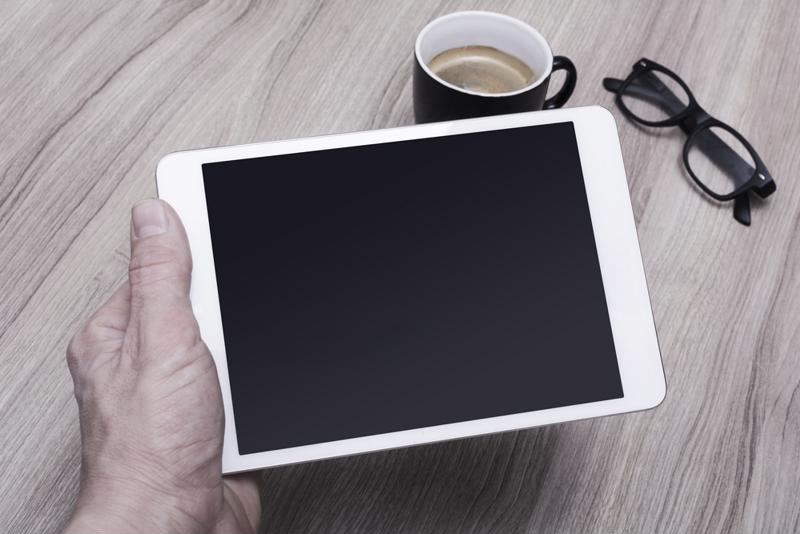 Person holding a tablet next to a cup of coffee.