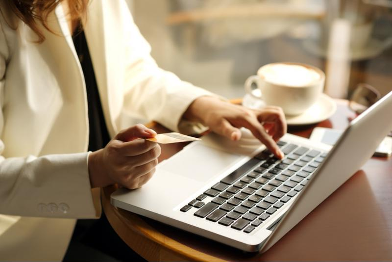 A person completes an online transaction from a laptop.