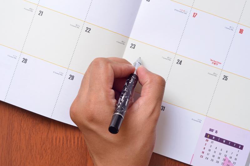 person holding pen marking calendar