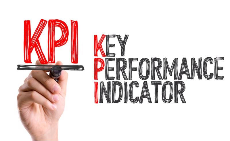 "A hand writes the words ""key performance indicator."""