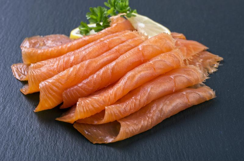 Smoked salmon pieces on black counter.