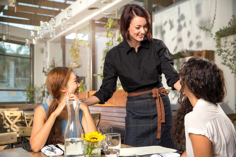 A server greets two guests in a restaurant.