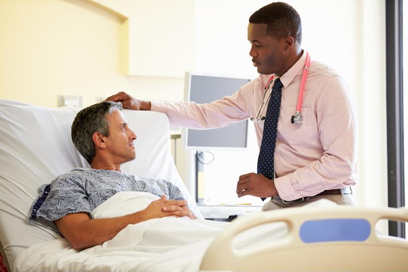 Doctor seeing patient in hospital bed.
