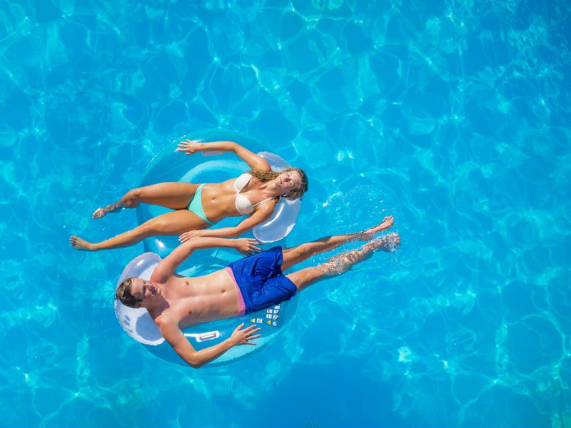 Couple floating on rafts in pool.