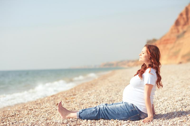 Pregnant woman sitting on a beach in front of the waves.