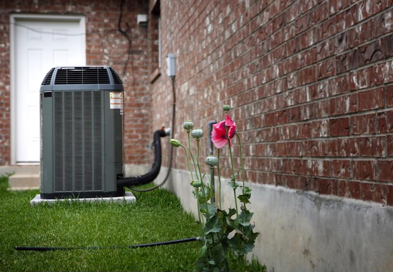 A/C condenser outside a brick house.