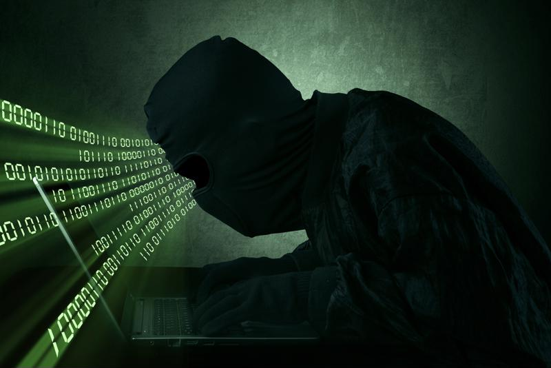 "Man in all black, mask and gloves typing at a keyboard surrounded by binary code - ""hacker."""