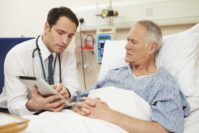 Doctor consulting with patient in hospital.