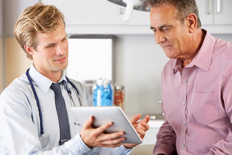 Doctor showing tablet to patient.