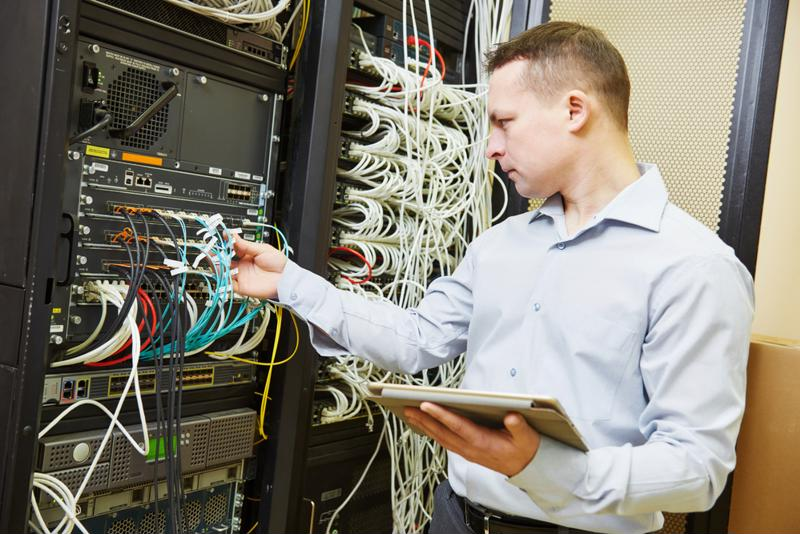 Data center worker checking network cables.