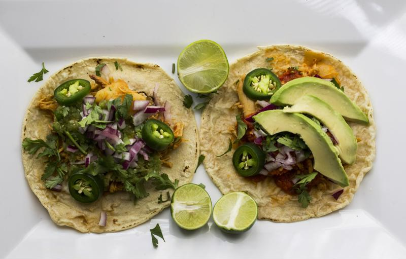 Top your pumpkin chicken tacos with lettuce, lime and avocado.