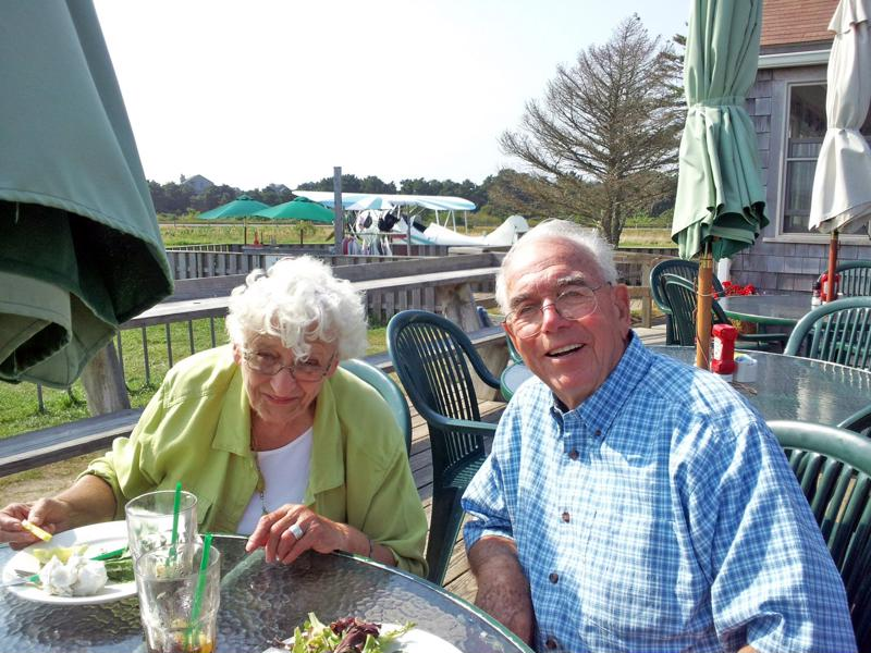 Senior couple eating salads outside assisted living community.