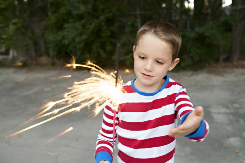 Young kid holding a sparkler in driveway.